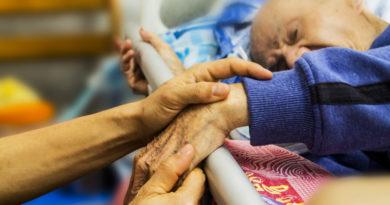 Pacjent hospicjum w łóżku trzyma rodzinę za rękę